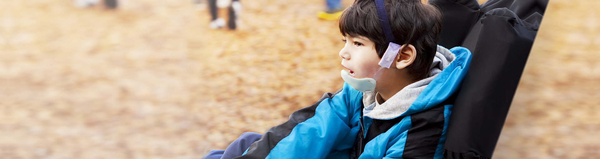 young boy watching other children play